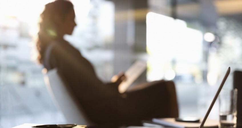 Businesswoman using digital tablet in lobby